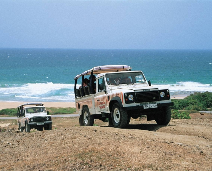 Island Safari Jeeps on hill with beach Barbados